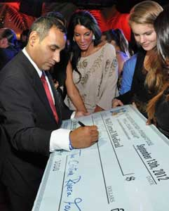 John  Gungie Rivera makes out a check for Dr. Mark Souweidane, 2012 Cristian Rivera Foundation Gala